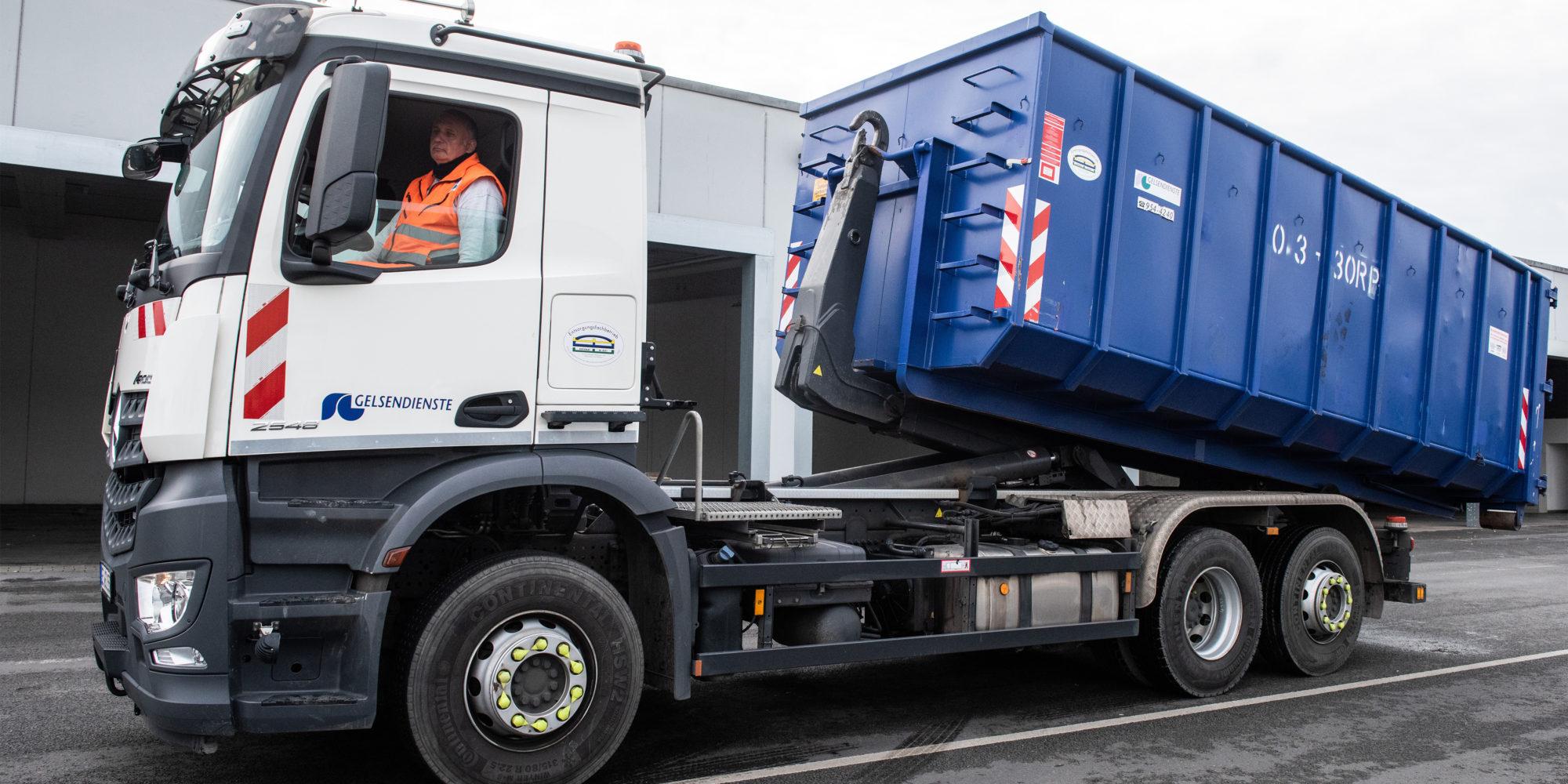 Ein GELSENDIENSTE Container wird von einem Fahrzeug abgerollt.