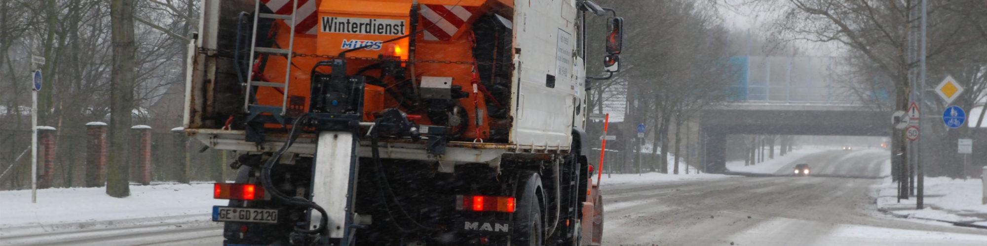 Streu- und Räumfahrzeug von GELSENDIENSTE im Winterdiensteinsatz auf der verschneiten Adenauerallee in Erle.