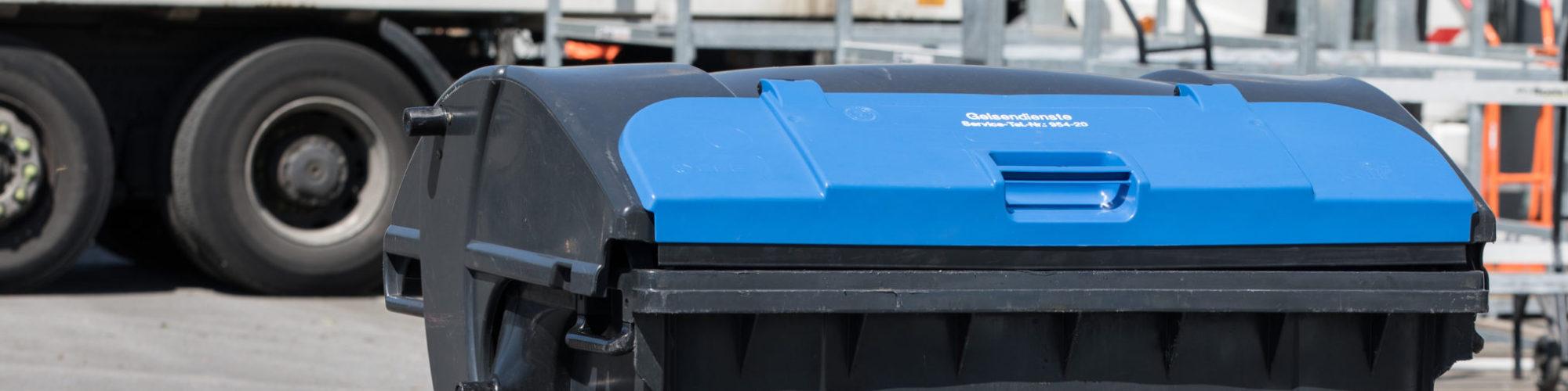 Blauer 1.100 Liter-Behälter für Altpapier mit vier Rädern und Schiebedeckel.