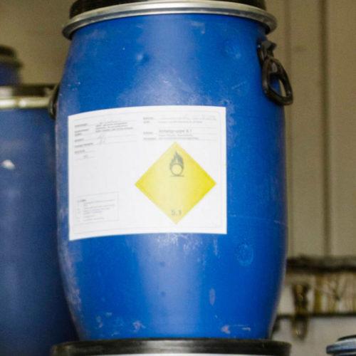 Eine Fachkraft für Kreislauf-und Abfallwirtschaft von GELSENDIENSTE sortiert Problemabfälle in blaue Behälter.